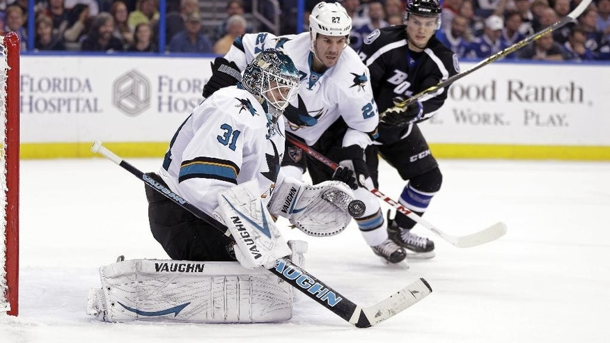 San Jose Sharks goalie Antti Niemi (31), of Finland, makes a save on a shot as defenseman Scott Hannan (27) keeps Tampa Bay Lightning left wing Jonathan Drouin (27) from a rebound during the second period of an NHL hockey game Thursday, Nov. 13, 2014, in Tampa, Fla. (AP Photo/Chris O'Meara)