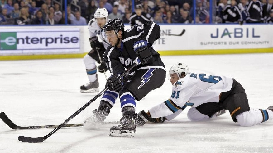 Tampa Bay Lightning right wing Ryan Callahan (24) cuts around San Jose Sharks defensemen Justin Braun (61) and Marc-Edouard Vlasic (44) as he goes to the goal during the second period of an NHL hockey game Thursday, Nov. 13, 2014, in Tampa, Fla. (AP Photo/Chris O'Meara)