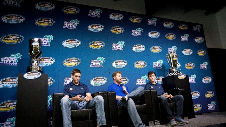 Crew chief Greg Ives, left, team owner Dale Earnhardt Jr, and driver Chase Elliott, right, talk about winning the Nationwide series championship during a press conference in Homestead, Fla, Thursday, Nov. 13, 2014. (AP Photo/J Pat Carter)