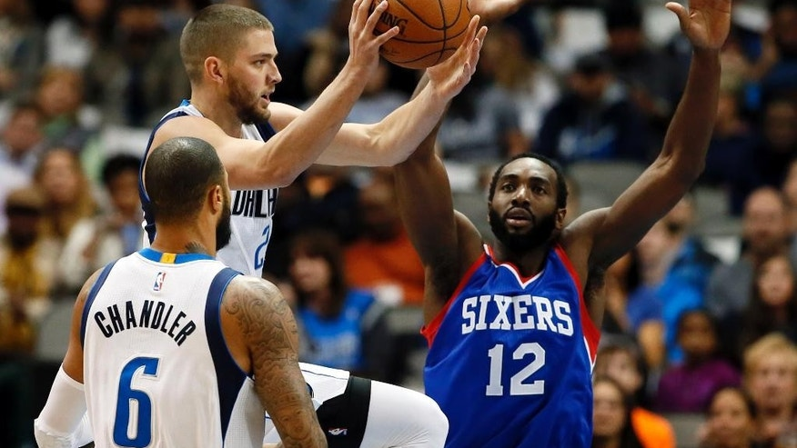 Dallas Mavericks' Chandler Parsons, top left, passes the ball in front of Tyson Chandler (6) as Philadelphia 76ers' Luc Richard Mbah a Moute (12) of Cameroon defends in the first half of an NBA basketball game, Thursday, Nov. 13, 2014, in Dallas. (AP Photo/Tony Gutierrez)