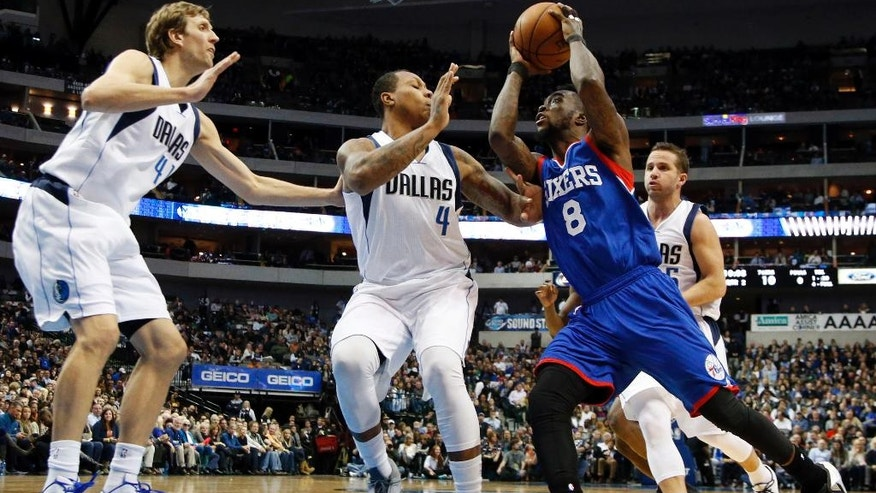 Philadelphia 76ers guard Tony Wroten (8) drives the base line against Dallas Mavericks' Dirk Nowitzki, left, of Germany and Greg Smith (4) after getting by the Mavericks' J.J. Barea, right rear, of Puerto Rico, for a shot opportunity in the first half of an NBA basketball game, Thursday, Nov. 13, 2014, in Dallas. (AP Photo/Tony Gutierrez)