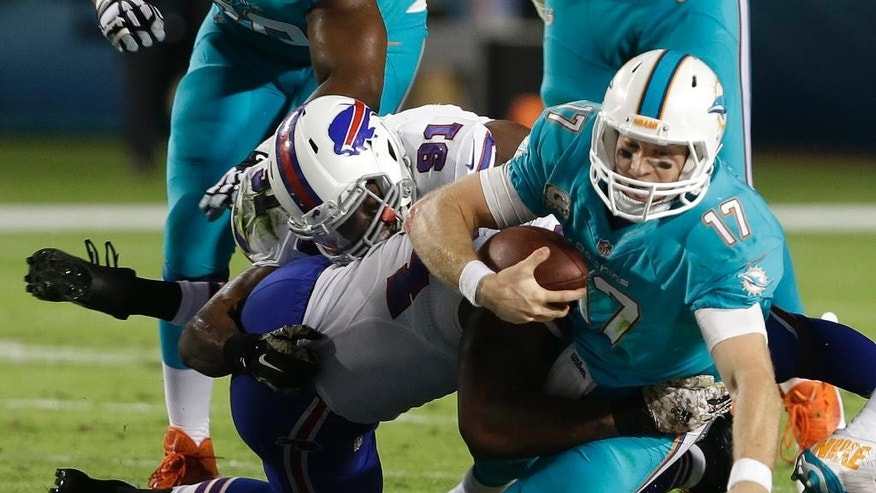 Miami Dolphins quarterback Ryan Tannehill (17) is sacked by Buffalo Bills defensive end Mario Williams (94) during the first half of an NFL football game, Thursday, Nov. 13, 2014, in Miami Gardens, Fla. (AP Photo/Lynne Sladky)