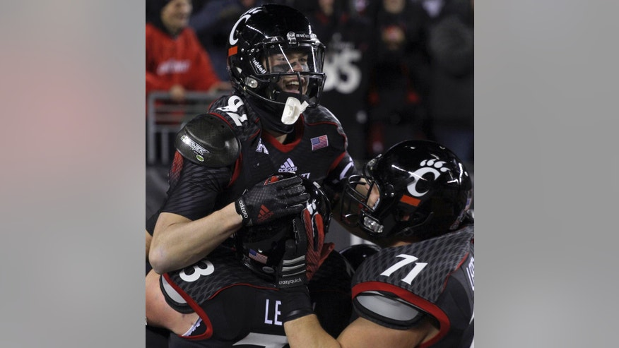 Cincinnati's Max Morrison, top, celebrates with teammates after scoring a touchdown against East Carolina in the first half of an NCAA college football game in Cincinnati, Thursday, Nov. 13, 2014. (AP Photo/Tom Uhlman)