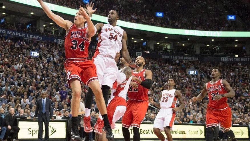 Chicago Bulls forward Mike Dunleavy (34) soars to the basket past Toronto Raptors' Patrick Patterson (54) during the second half of an NBA basketball game Thursday, Nov. 13, 2014, in Toronto. (AP Photo/The Canadian Press, Frank Gunn)