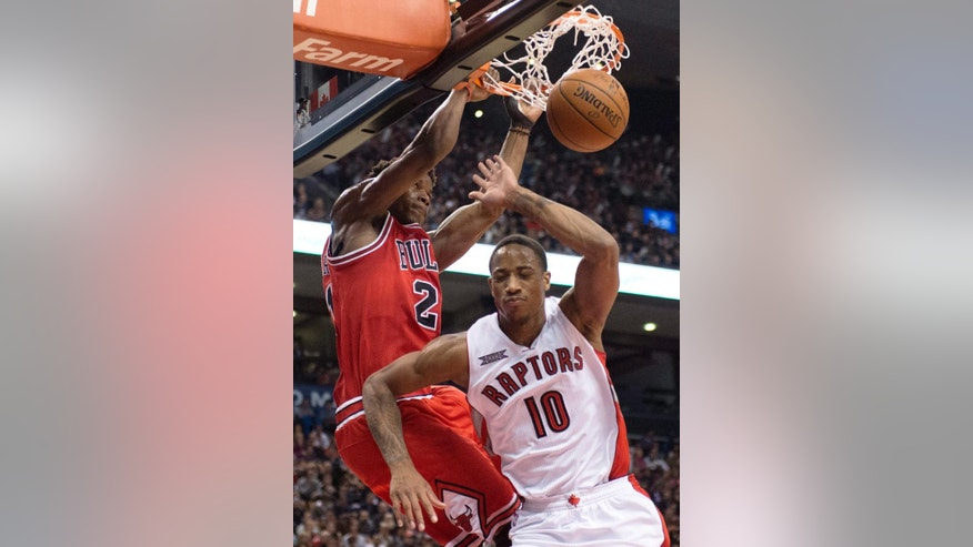Chicago Bulls guard Jimmy Butler dunks over Toronto Raptors guard DeMar DeRozan during the second half of an NBA basketball game Thursday, Nov. 13, 2014, in Toronto. (AP Photo/The Canadian Press, Frank Gunn)