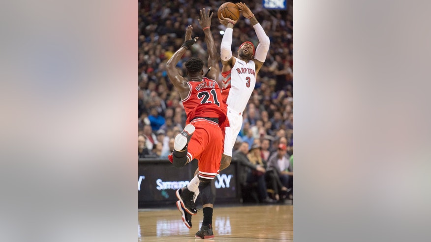 Toronto Raptors forward James Johnson (3) is fouled by Chicago Bulls guard Jimmy Butler (21) during the first half of an NBA basketball game Thursday, Nov. 13, 2014, in Toronto. (AP Photo/The Canadian Press, Frank Gunn)