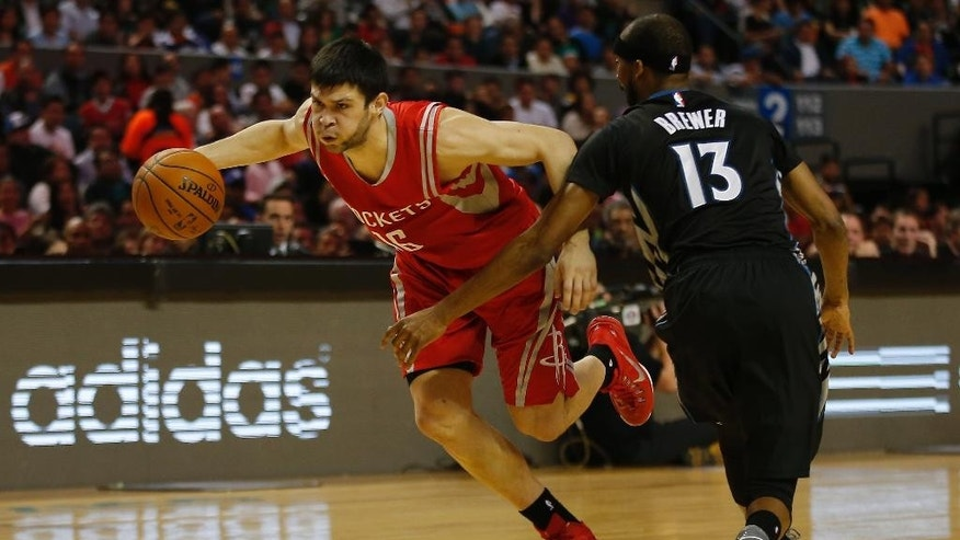 Houston Rockets' Kostas Papanikolau (16), left, drives past Minnesota Timberwolves' Corey Brewer (13) during the first half of an NBA basketball game in Mexico City, Wednesday, Nov. 12, 2014. (AP Photo/Eduardo Verdugo)