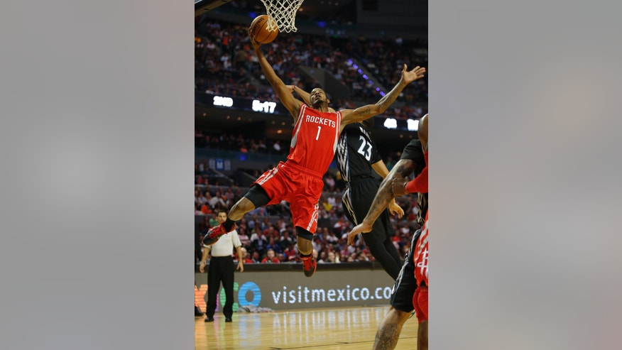 Houston Rockets' Trevor Ariza (1) attempts to make a basket as Minnesota Timberwolves' Kevin Martin (23) tries to block during an NBA basketball game in Mexico City, Wednesday, Nov. 12, 2014. (AP Photo/Eduardo Verdugo)