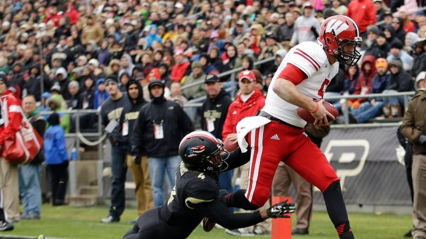 Wisconsin quarterback Tanner McEvoy, left, scores a touchdown in front of Purdue safety Taylor Richards (4) during the second half of an NCAA college football game in West Lafayette, Ind., Saturday, Nov. 8, 2014. Wisconsin won 34-16. (AP Photo/AJ Mast)