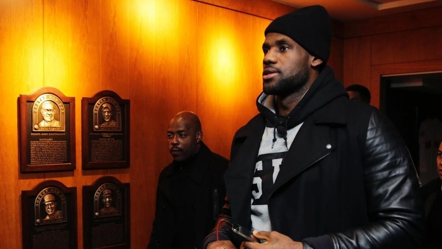 Cleveland Cavaliers' LeBron James passes plaques of inductees to the Boston Red Sox Hall of Fame as he arrives for a gathering at Fenway Park in Boston, Thursday, Nov. 13, 2014. James joined a business panel to discuss the ways sponsors and athletes try to engage fans in a digital age. (AP Photo/Charles Krupa)