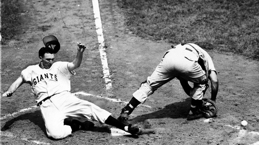 FILE - In this June 24, 1950, file photo, New York Giants' Alvin Dark slides safely across home plate as Cincinnati Reds catcher Dixie Howell cannot handle the throw on an inside-the-park home run in the second inning of a baseball game at the Polo Grounds in New York. Longtime manager and star shortstop Alvin Dark died Thursday, Nov. 13, 2014, at his home, according to the Robinson Funeral Home in Easley, S.C. (AP Photo/File)