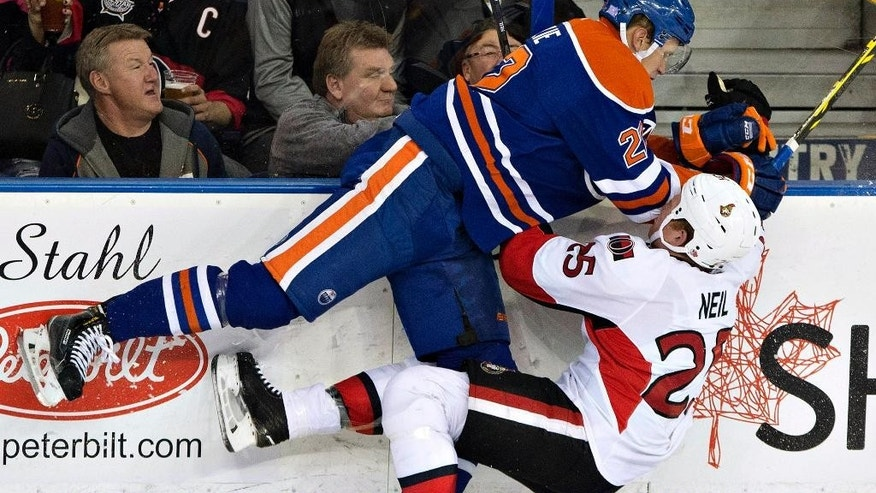 Ottawa Senators' Chris Neil (25) is checked by Edmonton Oilers' Keith Aulie (22) during the second period of an NHL hockey game Thursday, Nov. 13, 2014, in Edmonton, Alberta. (AP Photo/The Canadian Press, Jason Franson)