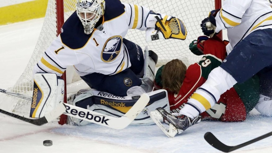 Buffalo Sabres goalie Jhonas Enroth, left, of Sweden, blocks a shot as Minnesota Wild's Mikael Granlund, center, of Finland crashes into him, losing his helmet, duirng the first period of an NHL hockey game, Thursday, Nov. 13, 2014, in St. Paul, Minn. (AP Photo/Jim Mone)