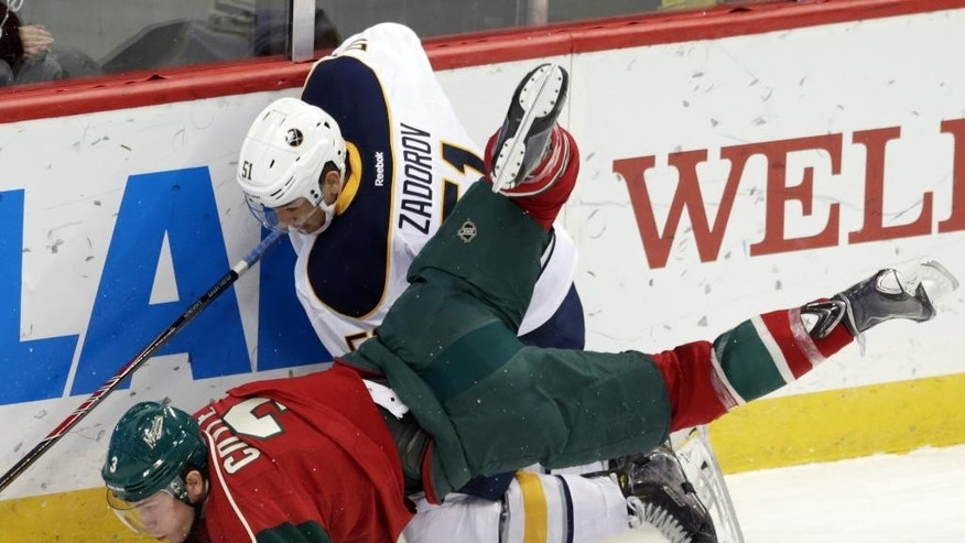 Minnesota Wild's Charlie Coyle, left, trips over Buffalo Sabres' Nikita Zadorov of Russia in a race for the puck during the first period of an NHL hockey game, Thursday, Nov. 13, 2014, in St. Paul, Minn. (AP Photo/Jim Mone)