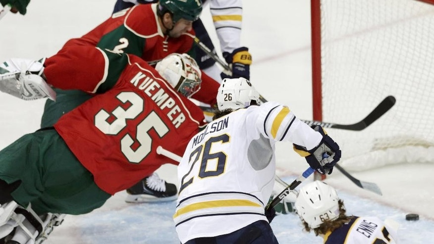 Minnesota Wild goalie Darcy Kuemper, left makes a futile try to stop the puck as Buffalo Sabres' Rasmus Ristolainen, not shown, of Finland, scores in the first period of an NHL hockey game, Thursday, Nov. 13, 2014, in St. Paul, Minn. (AP Photo/Jim Mone)