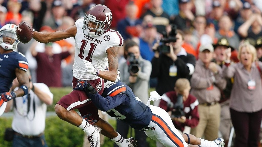 Texas A&M wide receiver Josh Reynolds (11) scores a touchdown against Auburn Auburn defensive back Johnathan Ford (23) during the first half of an NCAA college football game, Saturday, Nov. 8, 2014, in Auburn, Ala. (AP Photo/Brynn Anderson)