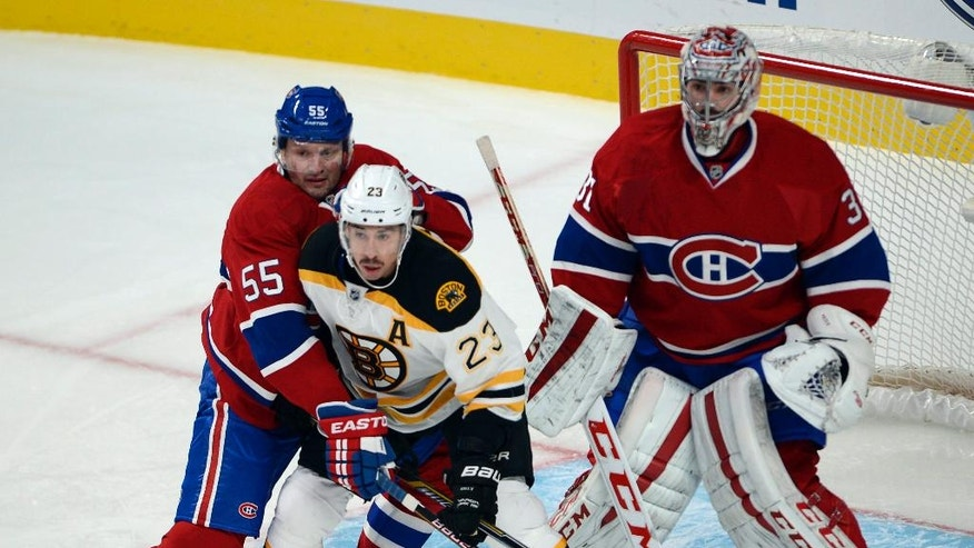 Montreal Canadiens defenseman Sergei Gonchar (55) ties up Boston Bruins center Chris Kelly (23) in front of Montreal Canadiens goalie Carey Price (31) during the first period of an NHL hockey game Thursday, Nov. 13, 2014, in Montreal. (AP Photo/The Canadian Press, Ryan Remiorz)
