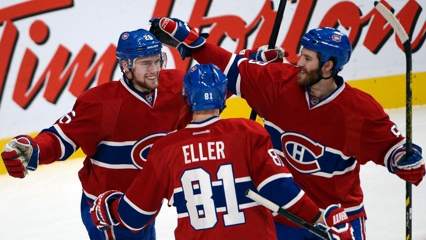Montreal Canadiens left wing Jiri Sekac, left, celebrates his goal with teammates Lars Eller and Brandon Prust, right, during the third period of an NHL hockey game against the Boston Bruins, Thursday, Nov. 13, 2014, in Montreal. (AP Photo/The Canadian Press, Ryan Remiorz)