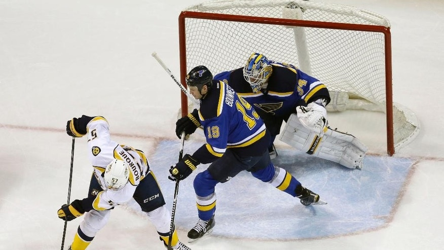 Nashville Predators' Gabriel Bourque, left, tries to control the puck as St. Louis Blues goalie Jake Allen and Jay Bouwmeester (19) defend during the second period of an NHL hockey game Thursday, Nov. 13, 2014, in St. Louis. (AP Photo/Jeff Roberson)