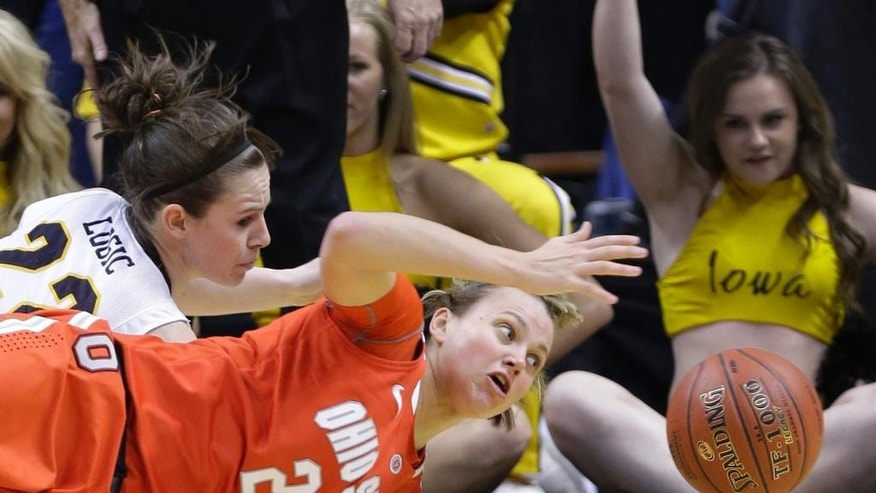 FILE - In this March 8, 2014 file photo, Ohio State guard Amy Scullion (25) and Iowa guard Samantha Logic go for a loose ball in the first half of an NCAA college basketball game in the semifinals of the Big Ten women's tournament in Indianapolis. Scullion had already graduated and been accepted into Ohio State's medical school. A starter a year ago, she's returning to a team that is short-handed because one player was kicked off the team and three others sustained season-ending knee injuries in the preseason. (AP Photo/Michael Conroy, File)