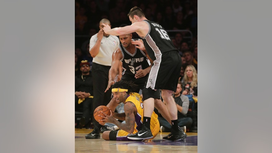Los Angeles Lakers' Jordan Hill, bottom, gets a loose ball against San Antonio Spurs' Aron Baynes, right, and Boris Diaw during the first half of an NBA basketball game Friday, Nov. 14, 2014, in Los Angeles. (AP Photo/Jae C. Hong)