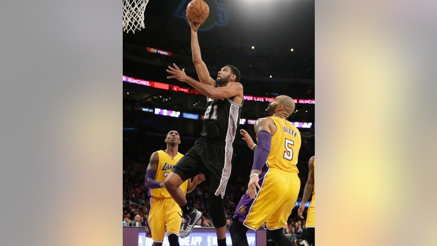 San Antonio Spurs' Tim Duncan, center, goes up for a basket as Los Angeles Lakers' Kobe Bryant, left, and Carlos Boozer watch during the first half of an NBA basketball game Friday, Nov. 14, 2014, in Los Angeles. (AP Photo/Jae C. Hong)