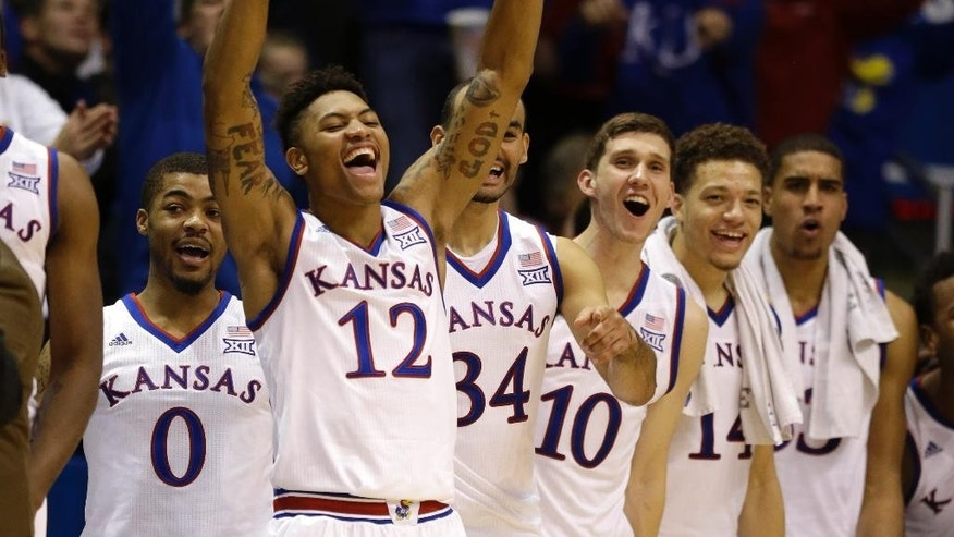 Kansas guard Kelly Oubre Jr. (12) leads the celebration of a three-point basket by guard Evan Manning during the second half of an exhibition college basketball game in Lawrence, Kan., Tuesday, Nov. 11, 2014. Kansas defeated Emporia State 109-56. (AP Photo/Orlin Wagner)