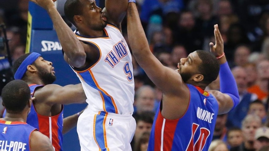 Oklahoma City Thunder's Serge Ibaka (9) grabs a rebound in front of Detroit Pistons' Greg Monroe (10) during the first quarter of an NBA basketball game in Oklahoma City, Friday, Nov. 14, 2014. (AP Photo/Sue Ogrocki)