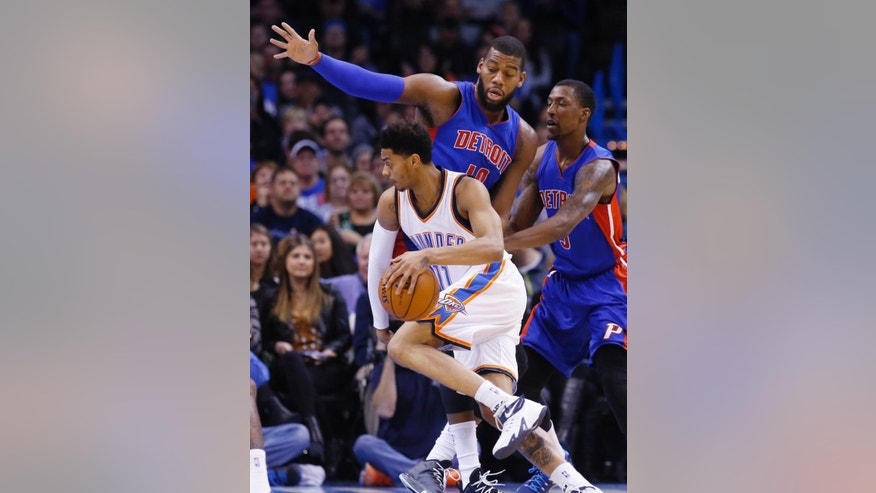 Oklahoma City Thunder's Jeremy Lamb (11) drives past Detroit Pistons' Greg Monroe (10) and Kentavious Caldwell-Pope, right, during the first quarter of an NBA basketball game in Oklahoma City, Friday, Nov. 14, 2014. (AP Photo/Sue Ogrocki)