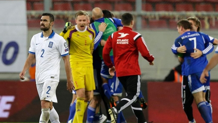 Greece's Giannis Maniatis leaves the pitch as Faroe Islands' players celebrate after the Group F Euro 2016 qualifying soccer match between Greece and Faroe Islands, at the Georgios Karaiskakis stadium, in the port of Piraeus, near Athens on Friday, Nov. 14, 2014. Faroe Islands won 1-0. (AP Photo/Thanassis Stavrakis)