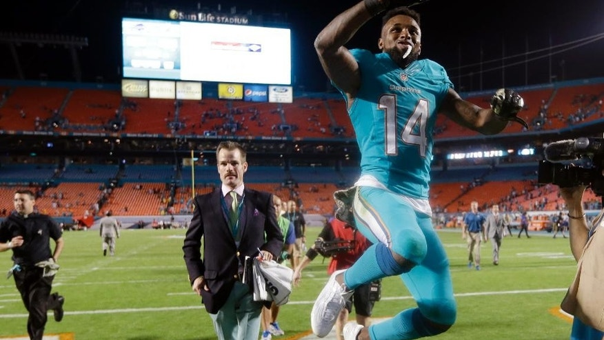 Miami Dolphins wide receiver Jarvis Landry (14) leaps as he leaves the field after the Dolphins' NFL football game against the Buffalo Bills, Thursday, Nov. 13, 2014, in Miami Gardens, Fla. The Dolphins defeated the Bills 22-9. (AP Photo/Lynne Sladky)