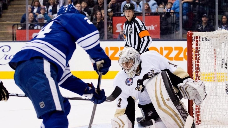 Pittsburgh Penguins goaltender Thomas Greiss, right, makes a save on Toronto Maple Leafs' Peter Holland during the second period of NHL hockey action in Toronto on Friday, Nov. 14, 2014. (AP Photo/The Canadian Press, Darren Calabrese)