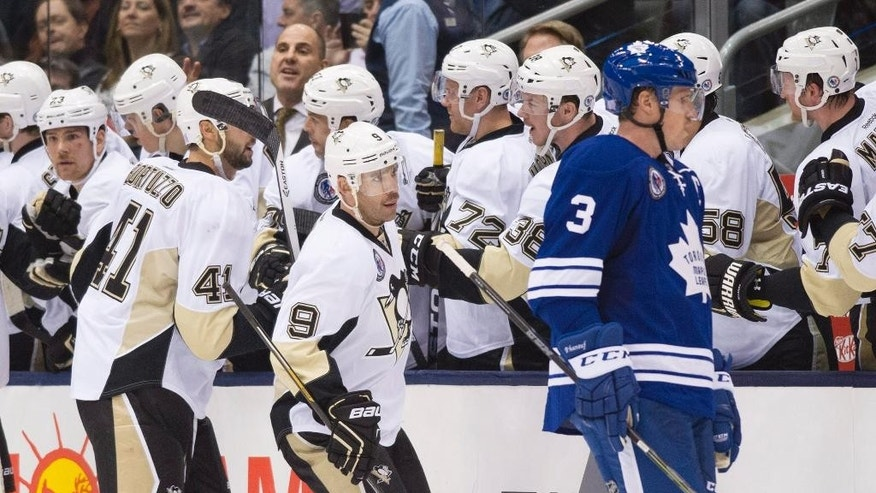 Pittsburgh Penguins' Pascal Dupuis, center, celebrates his goal with teammates in front of Toronto Maple Leafs' Dion Phaneuf during second period NHL hockey action in Toronto on Friday, Nov. 14, 2014. (AP Photo/The Canadian Press, Darren Calabrese)