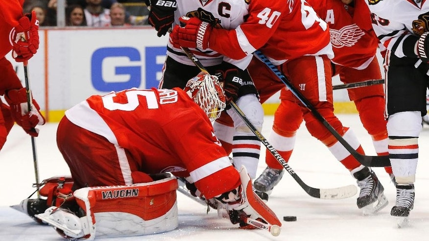Detroit Red Wings left wing Henrik Zetterberg (40) wraps Chicago Blackhawks center Jonathan Toews (19) up as goalie Jimmy Howard (35) stops a shot in the third period of an NHL hockey game in Detroit, Friday, Nov. 14, 2014. Detroit won 4-1. (AP Photo/Paul Sancya)