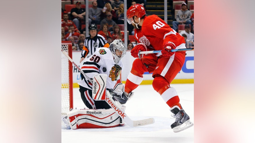 Detroit Red Wings left wing Henrik Zetterberg (40), jumps as Chicago Blackhawks goalie Corey Crawford (50) stops a shot in the second period of an NHL hockey game in Detroit, Friday, Nov. 14, 2014. (AP Photo/Paul Sancya)