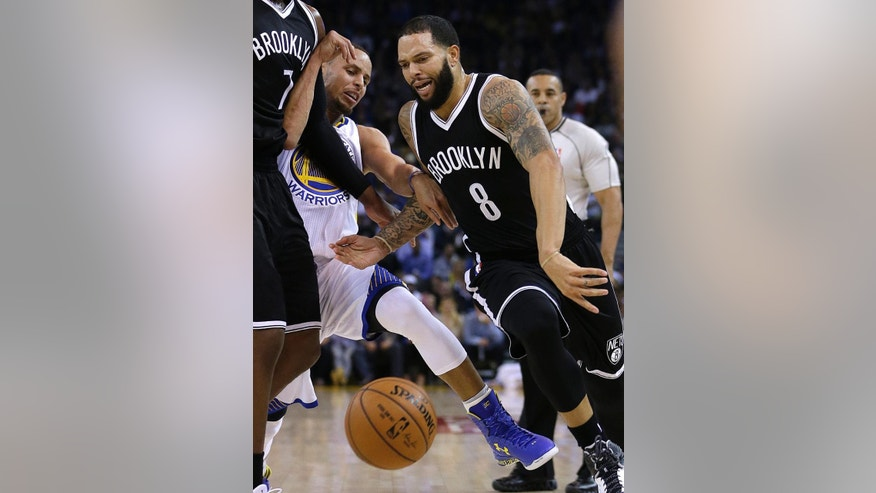 Brooklyn Nets' Deron Williams (8) drives the ball past Golden State Warriors' Stephen Curry during the first half of an NBA basketball game Thursday, Nov. 13, 2014, in Oakland, Calif. (AP Photo/Ben Margot)