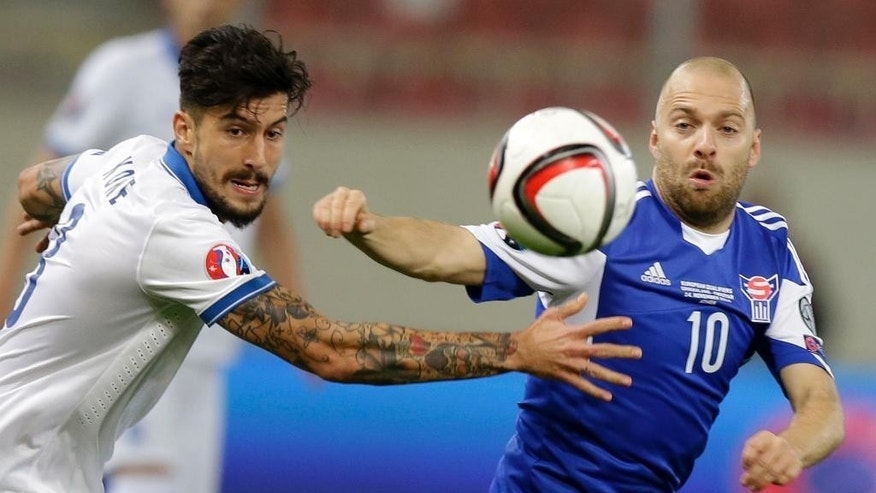 Greece's Panagiotis Kone, left, fights for the ball with Faroe Islands' Christian Holst during the Group F Euro 2016 qualifying soccer match between Greece and Faroe Islands, at the Georgios Karaiskakis stadium, in the port of Piraeus, near Athens, Friday, Nov. 14, 2014. (AP Photo/Thanassis Stavrakis)