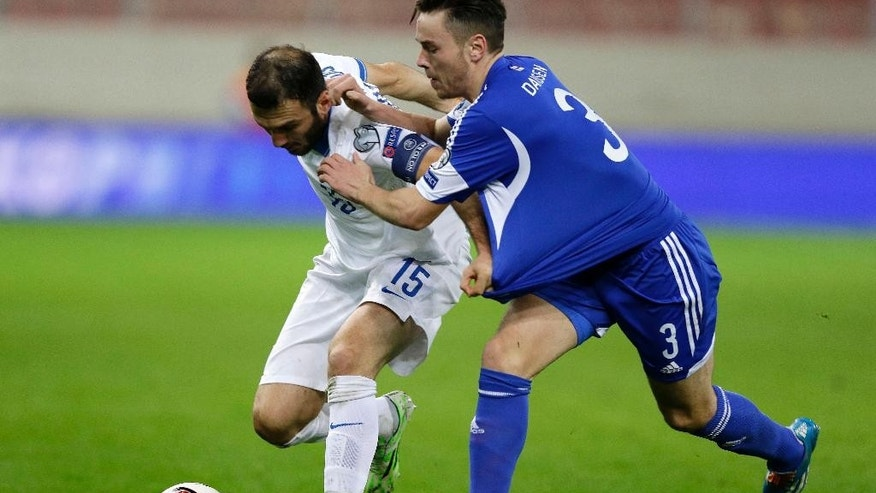 Greece's Vasilis Torosidis, left, fights for the ball with Faroe Islands' Vijormur Davidsen during the Group F Euro 2016 qualifying soccer match between Greece and Faroe Islands, at the Georgios Karaiskakis stadium, in the port of Piraeus, near Athens on Friday, Nov. 14, 2014. (AP Photo/Thanassis Stavrakis)