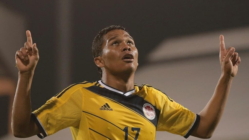 Colombia's Carlos Bacca, celebrates after scoring against USA, during an international friendly soccer match at the Craven Cottage ground in London, Friday, Nov. 14, 2014. (AP Photo/Lefteris Pitarakis)