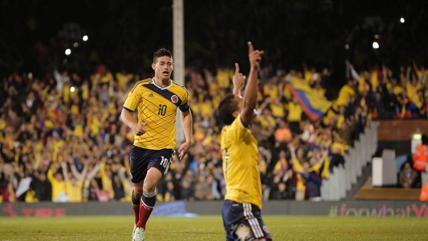 Colombia's captain James Rodriguez, left, runs to celebrate with his teammate Carlos Bacca, right, after Bacca scored against USA, during an international friendly soccer match at the Craven Cottage ground in London, Friday, Nov. 14, 2014. Colombia won the match 2-1(AP Photo/Lefteris Pitarakis)