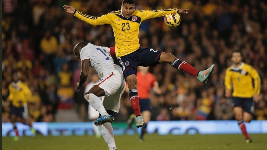 Colombia's Jeison Murillo, top, jumps for the ball with USA's captain Josy Altidore, left, during an international friendly soccer match against USA at the Craven Cottage ground in London, Friday, Nov. 14, 2014. (AP Photo/Lefteris Pitarakis)