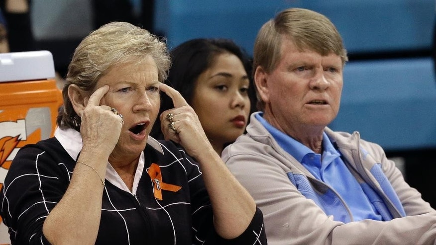 North Carolina coach Sylvia Hatchell, left, directs her team during the first half of an NCAA college basketball game against Howard in Chapel Hill, N.C., Friday, Nov. 14, 2014. Hatchell returned to the court to coach her first regular season game since being treated for cancer. Associate coach Andrew Calder, right, looks on. (AP Photo/Gerry Broome)