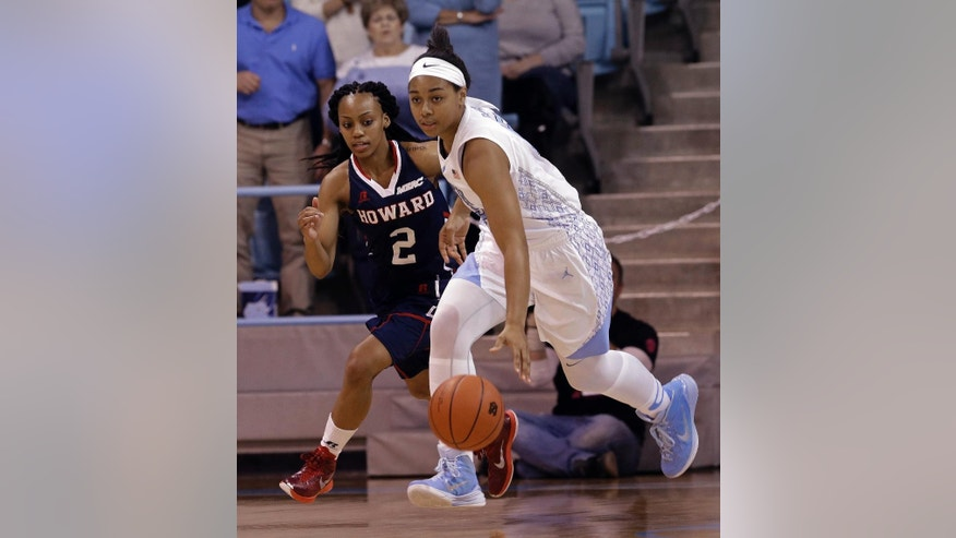 North Carolina's Allisha Gray dribbles the ball as Howard's Te'Shya Heslip (2) chases during the first half of an NCAA college basketball game in Chapel Hill, N.C., Friday, Nov. 14, 2014. (AP Photo/Gerry Broome)