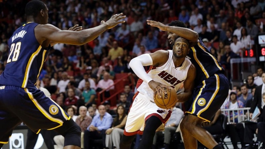 Miami Heat's Dwyane Wade, center, drives to the basket as Indiana Pacers' Ian Mahinmi (28) and Solomon Hill, right, defend in the second half of an NBA basketball game, Wednesday, Nov. 12, 2014, in Miami. The Pacers won 81-75. (AP Photo/Lynne Sladky)