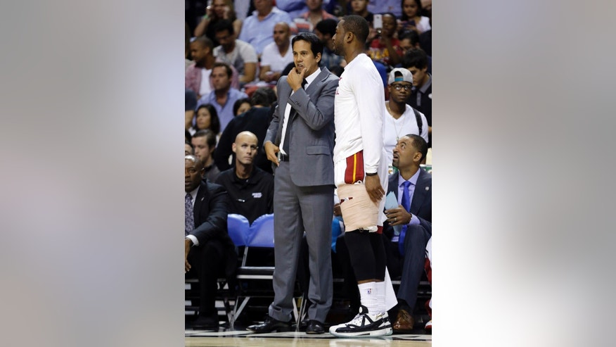 Miami Heat head coach Erik Spoelstra, left, talks with Dwyane Wade, right, in the first half of an NBA basketball game against the Indiana Pacers, Wednesday, Nov. 12, 2014, in Miami. (AP Photo/Lynne Sladky)