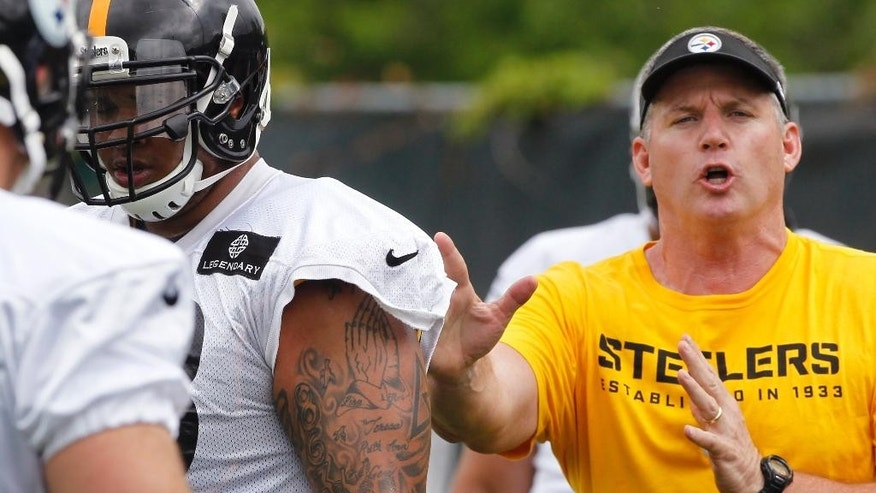 In this photo from May 28, 2014, Pittsburgh Steelers offensive line coach Mike Munchak, right, gives instruction during an NFL football organized team activity in Pittsburgh. Fired by the only NFL organization he's ever called home after going 22-26 as head coach from 2011-13, Munchak now finds himself preparing the Pittsburgh Steelers offensive line to face a roster filled with players he either drafted, developed or both, with the Titans.   (AP Photo/Keith Srakocic)
