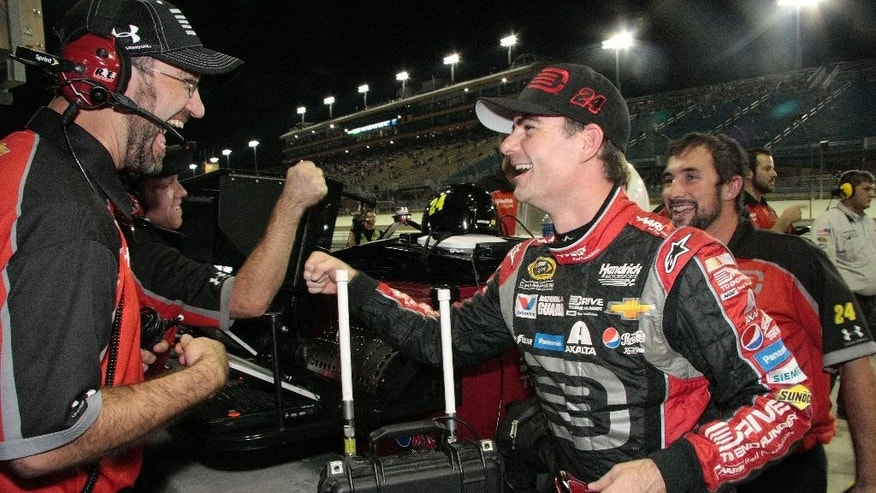 Jeff Gordon, front right, celebrates after qualifying laps for the EcoBoost 400 auto race, Friday, Nov. 14, 2014, in Homestead, Fla. Gordon won the pole position. (AP Photo/Darryl Graham)