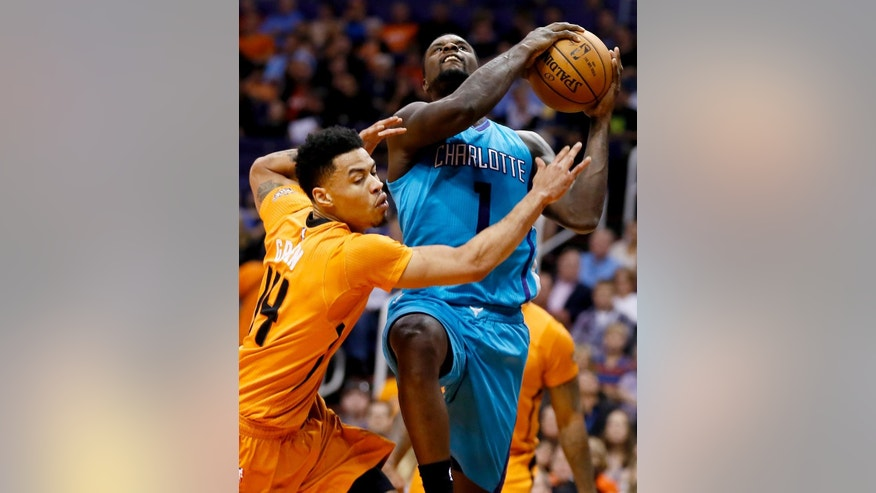 Charlotte Hornets guard Lance Stephenson (1) is fouled by Phoenix Suns guard Gerald Green (14) during the first half of an NBA basketball game, Friday, Nov. 14, 2014, in Phoenix. (AP Photo/Matt York)