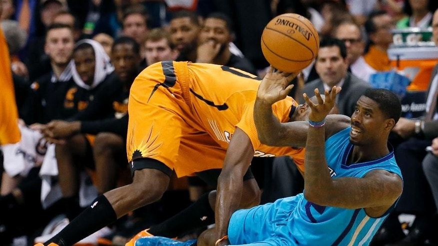 Charlotte Hornets forward Marvin Williams passes under pressure from Phoenix Suns forward Anthony Tolliver during the first half of an NBA basketball game, Friday, Nov. 14, 2014, in Phoenix. (AP Photo/Matt York)