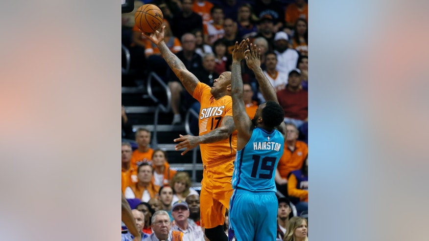 Phoenix Suns forward P.J. Tucker (17) shoots over Charlotte Hornets guard P.J. Hairston (19) during the first half of an NBA basketball game, Friday, Nov. 14, 2014, in Phoenix. (AP Photo/Matt York)